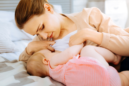 Concentrated mother during breastfeeding her baby Stock Photo
