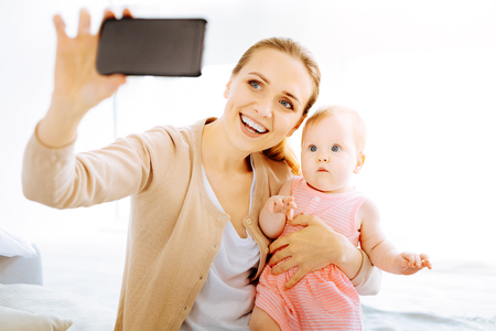 Funny baby looking surprised while seeing a smartphone