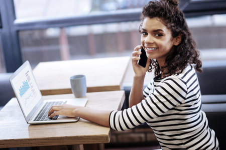 Exuberant curly-haired girl talking on the phone Stock Photo