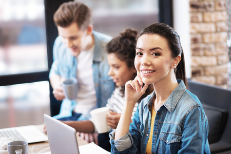 Nice girl sitting with her laptop and smiling Stock Photo