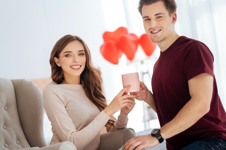 Beaming couple smiling while warming up with aromatic tea Stock Photo