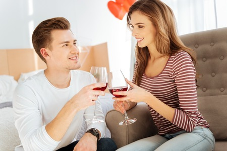 Beaming young couple drinking red wine at home