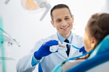 Joyful professional dentist showing the technique of brushing teeth