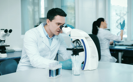Confident male person working with microscope Stock Photo