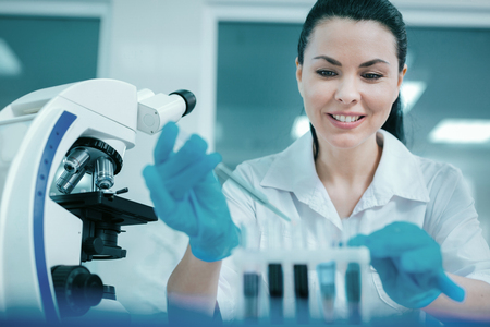 up code: Positive female scientist doing chemical experiment