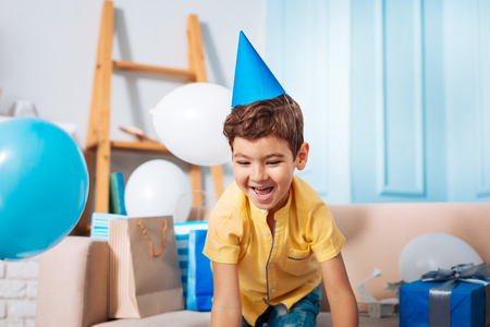 Upbeat mood. Happy adorable boy laughing and leaning forward as if lifting some toy while being in a room full of his birthday presents Stock Photo
