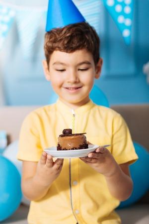 おいしいケーキ。それと、ろうそくを吹き消すために準備ができている彼の誕生日ケーキのプレートを保持パーティー ハットで陽気な少年