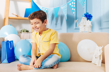 Enormous happiness. Adorable little boy sitting on the sofa surrounded by balloons and birthday presents and smiling broadly and happily while wearing a party hat Stock Photo