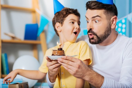 upbringing: Goofing around. Cheerful young man and his upbeat son blowing out a candle on a birthday cake and having fun, making funny faces, while the boy looking at his father Stock Photo
