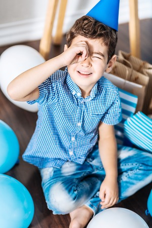 Wannabe pirate. Adorable little boy sitting on the floor and holding his hand near his eye as if imitating a spyglass while wearing a party hat