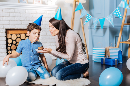 Tender care. Beautiful young woman sitting on her knees near her little son and blowing out candles on his birthday cake together with him Stock Photo
