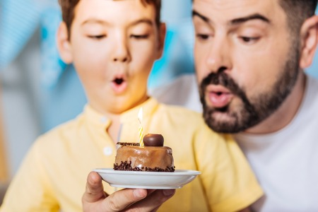 Delicious gift. The focus being on the plate with a cake and a lit candle while cheerful father and son blowing out the candle, celebrating birthday