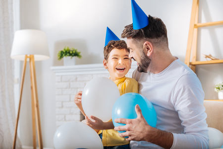 Treasured moments. Pleasant young man and his little son sitting on the sofa, holding balloon and laughing while talking to each other