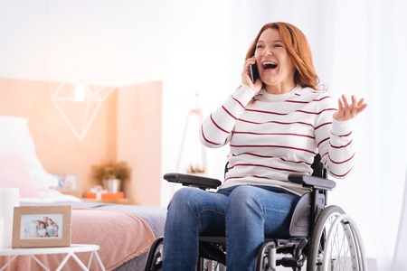 Great news. Joyful blond disabled woman smiling and talking on her phone while sitting in the wheelchair Stock Photo