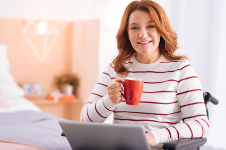 Being a freelancer. Attractive smiling blond disabled woman of middle age holding her cup and using her laptop while sitting in the wheelchair Stock Photo