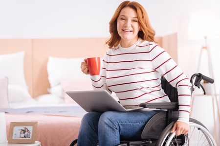 Coffee time. Pretty beaming blond disabled woman of middle age holding her cup and her laptop while sitting in the wheelchair Imagens