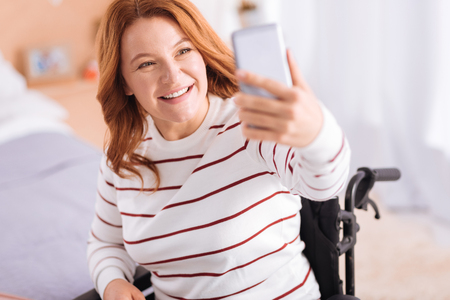 Say cheese. Attractive happy blond handicapped woman smiling and taking photos while sitting in a wheelchair