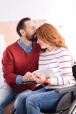 My precious. Loving bearded man and disabled woman of middle age kissing and holding hands and she holding a tablet while sitting in the wheelchair
