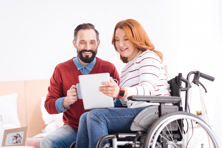 Showing pictures. Cheerful bearded man holding cups and alive disabled woman of middle age holding a tablet while she sitting in the wheelchair and they smiling Stock Photo