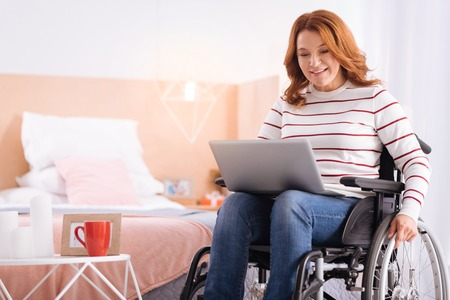 Being a freelancer. Beautiful alert blond woman of middle age smiling and holding laptop while sitting in the wheelchair