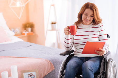 Coffee break. Attractive smiling blond disabled woman of middle age holding her cup and a notebook while sitting in the wheelchair Stock Photo