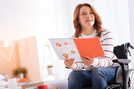 I like reading. Good-looking alert blond disabled woman of middle age smiling and holding a notebook while sitting in the wheelchair Stock Photo