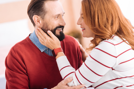 I cherish you. Loving bearded man and happy blond woman of middle age smiling and caressing each other and he hugging her