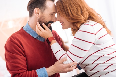 I treasure you. Alert caring bearded man and happy blond woman of middle age smiling and caressing each other and he hugging her Stock Photo