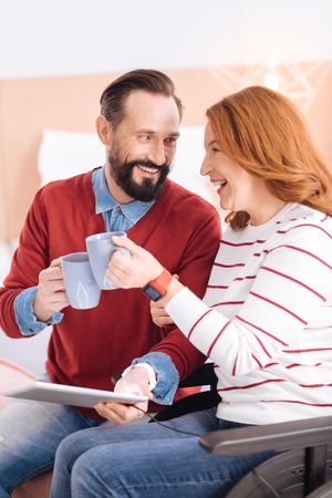 To us. Loving bearded man and disabled woman of middle age smiling at each other and holding cups and he holding a tablet while she sitting in the wheelchair Stock Photo