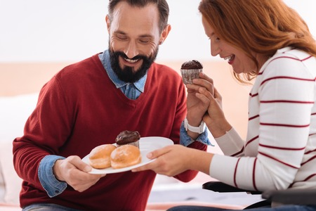 Having a dessert. Joyful bearded man and blond woman laughing and holding together a plate with some cookies and the woman holding the mans hand