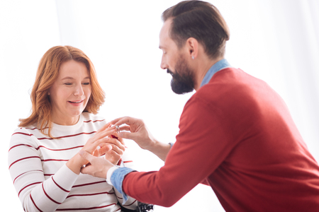 Forever together. Attractive joyful blond woman of middle age smiling and accepting the proposal while her future husband putting the ring on her finger