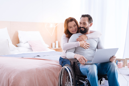 We love cuddling. Blond woman of middle age and a bearded disabled man smiling while the woman hugging him and the man sitting in a wheelchair with a laptop