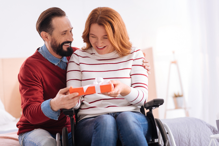 Happy Birthday. Bearded beaming man giving a present to a cheerful disabled blond woman of middle age and she smiling and looking at it while sitting in a wheelchair