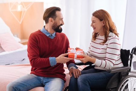 Present for you. Glad bearded man giving a present to a happy disabled woman of middle age and they holding it together and smiling at each other