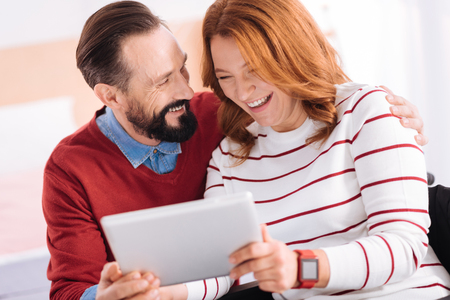 Having fun together. Joyful caring bearded man and pretty woman of middle age smiling and using a tablet and he hugging her Stock Photo