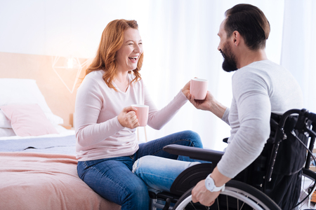 We love tea. Alert blond woman and a bearded disabled man laughing and looking at each other and holding cups while the man sitting in the wheelchair and the woman sitting on the couch