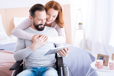 Doing things together. Gleeful blond woman of middle age and a bearded disabled man smiling and looking at the screen while the woman hugging him and the man sitting in a wheelchair with a tablet