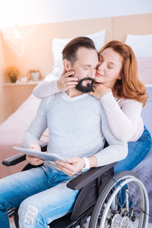 My treasure. Content blond woman of middle age and a bearded handicapped man holding a tablet while she hugging and caressing him from behind and their eyes closed