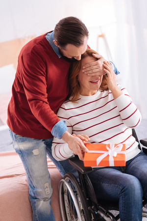 Surprise for you. Man making a surprise for a blond happy smiling differently able woman and the man closing her eyes with his one hand and holding a gift in another Stock Photo