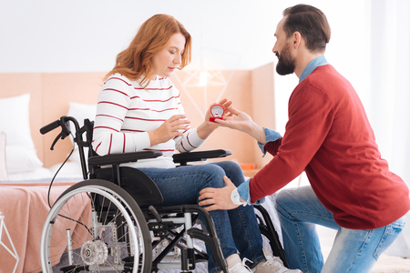 Making a proposal. Bearded man proposing to an attractive surprised blond handicapped woman accepting the ring and expressing astonishment while sitting in a wheelchair