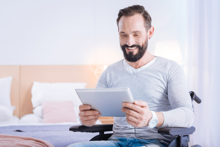 Relaxing. Alert bearded disabled man smiling and holding a tablet while sitting in a wheelchair