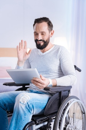 Talking to friends. Glad smiling bearded disabled man waving at the screen while using a tablet and sitting in a wheelchair