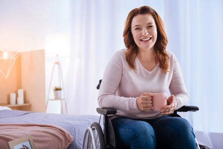 Happy moment. Exuberant blond disabled woman of middle age laughing and holding a cup while sitting in the wheelchair and a bed in the background Stock Photo