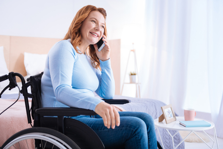 Great news. Joyful blond handicapped woman of middle age smiling and talking on her phone while sitting in the wheelchair and wearing a blue sweater