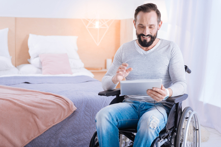 Playing computer games. Content cute bearded disabled man smiling and holding a tablet while sitting in a wheelchair