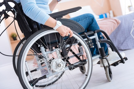 Wheelchair. Paralyzed woman sitting in a wheelchair and wearing a watch and having jeans and sneakers on
