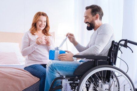 Opening the gift. Bearded disabled man opening a present while sitting in a wheelchair and a smiling woman sitting on the couch and holding a cup Stock Photo