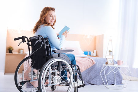 My favourite book. Joyful pretty blond handicapped woman of middle age smiling and holding a book while sitting in a wheelchair in a blue sweater and a bed in the background