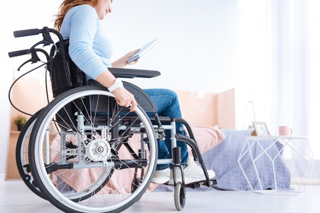 Avid reader. Blond smiling handicapped woman of middle age wearing a watch and a blue sweater and holding a book while sitting in a wheelchair Imagens - 89310965