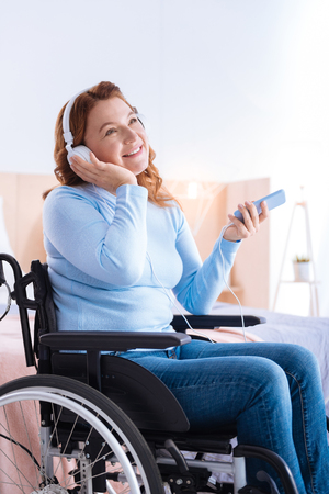 Listening to music. Gleeful attractive blond disabled woman of middle age smiling and wearing headset and holding her phone while sitting in the wheelchair in a blue sweater